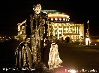 A statue of Hungarian actor Jozsef Timar and the new Hungarian National Theater are illuminated