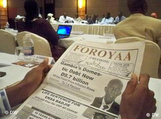Shot of two hands holding a Gambian newspaper