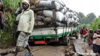 A man walks along a muddy path as a large, overloaded truck tries to negotiate what must serve as a road