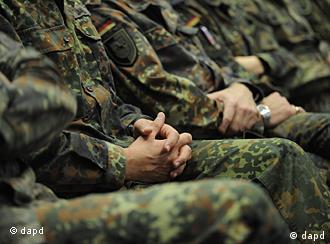 A row of sitting soldiers with folded hands