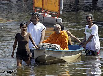 Thai Buddhist monk sitting on a boat, evacuates from a flooded area in Bangkok on Thursday, Oct. 27, 2011. Residents poured out of the Thai capital by bus, plane and train Thursday, heeding government warnings to use a special five-day holiday to evacuate parts of the flood-threatened metropolis before a weekend deluge rushes through.(Foto:Sakchai Lalit/AP/dapd)