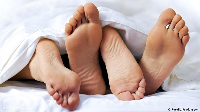 Close-up of the feet of a couple on the bed