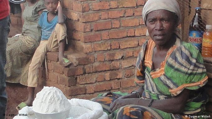 A closeup of a woman sitting with a sack full of flour