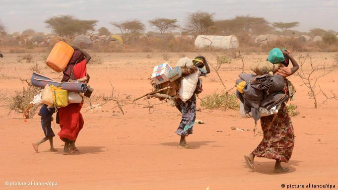 Women struggling through the desert with their belongings on their backs (picture alliance/dpa)