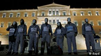 Protesters in prisoner costumes stand outside government