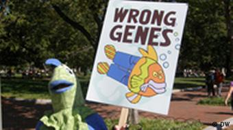 A person in a fish suit holding a sign that says 'wrong genes'