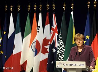 Merkel at G20 summit standing in front of national flags