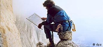 Messner lee un periódico sentado sobre una roca, a una altura que apunaría a muchos.