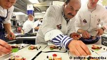 Sternekoch Johann Lafer (M) richtet am 27.06.2010 auf seiner Stromburg in Stromberg (Landkreis Bad Kreuznach) Teller an. Bei vielen jungen Leuten stehe es sehr schlecht um den guten Geschmack, findet der gebürtige Österreicher. Der Spitzenkoch hat einen Lehrauftrag in Kulinaristik, Esskultur und Kochkunst an der Hochschule in Fulda, wo er mit Ökotrophologen an Konzepten für die Geschmacksbildung arbeitet. Ziel ist, mehr Qualität in die Schulküchen zu bringen. Foto: Ulrich Perrey (zu dpa-Korr Kochen mit Mission... vom 05.07.2010) +++(c) dpa - Bildfunk+++