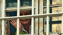 Former Ukrainian Prime Minister Yulia Tymoshenko waves to supporters from a prison window in Kiev, Ukraine, Friday, Nov. 4, 2011. Efforts to free jailed Ukrainian Prime Minister Yulia Tymoshenko suffered another setback after lawmakers delayed voting on a legal reform that could allow her release. (AP Photo/Ukrafoto)