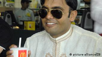 A man wearing sunglasses and a white kurta is smiling as he sits with a soft drink in a McDonald's restaurant in Varanasi. (Photo: Karlheinz Schindler)