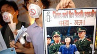 Zwei Demonstranten tragen OP-Masken mit einer durchgestrichnen Schlinge. Einer hält ein Protestplakat mit dem Foto einer Verurteilten kurz vor ihrer Hinrichtung (Quelle: AP).