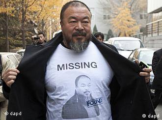 Chinese dissident artist Ai Weiwei opens his jacket to reveal a shirt bearing his portrait as he walks into the Beijing Local Taxation Bureau, China, Wednesday, Nov. 16, 2011. Ai went to the local tax bureau to fill in paperwork for a $1.3 million guarantee, and told reporters he feels like he was paying a ransom. (Foto:Andy Wong/AP/dapd)