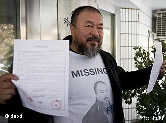 Chinese dissident artist Ai Weiwei shows his tax guarantee slips as he leaves the the Beijing Local Taxation Bureau, China, Wednesday, Nov. 16, 2011. Ai went to the local tax bureau to fill in paperwork for a $1.3 million guarantee, and told reporters he feels like he was paying a ransom. (Foto:Andy Wong/AP/dapd)