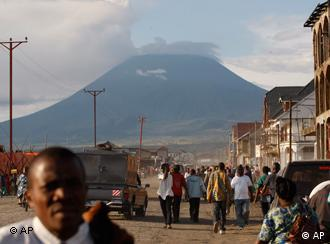 In this March 29, 2010 photo, residents walk along a central street in Goma, Congo, against the backdrop of Mount Nyiragongo, one of Africa's most active volcanos. Mount Nyiragongo is the ultimate symbol of death in Goma, the lakeside city it shadows and has overrun several times. Yet it's also a symbol of rebirth and resilience for a nation slowly emerging from war. In March, park rangers cleared Rwandan militias from its slopes and reopened the summit for the first time in a year and a half. (AP Photo/Rebecca Blackwell)