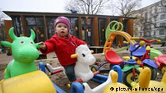 Dijete na dječjem igralištu jaši na jednoj spravi za igranje