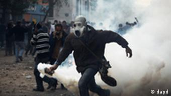 A protester throws a gas canister towards Egyptian riot police