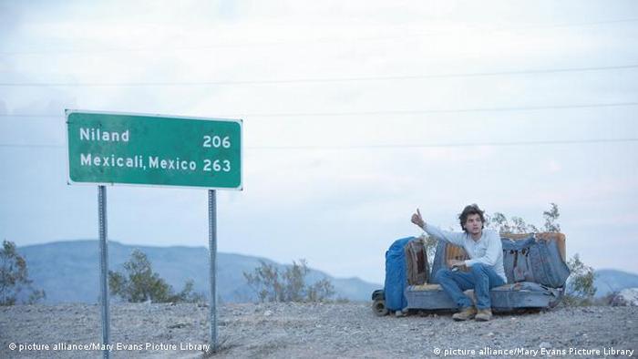 Film Into the Wild von Sean Penn - Szene mit jungem Mann an US-Strasse sitzend auf Sofa trampend (picture alliance/Mary Evans Picture Library)