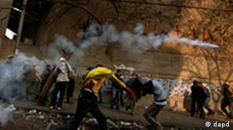 A Protester throws a tear gas canister away during clashes with the Egyptian riot police near Tahrir square in Cairo, Egypt, Tuesday, Nov. 22, 2011. Egypt's civilian Cabinet has offered to resign after three days of violent clashes in many cities between demonstrators and security forces, but the action failed to satisfy protesters deeply frustrated with the new military rulers. (Foto:Khalil Hamra/AP/dapd)