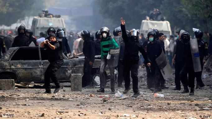 An Egyptian riot police officer, center, throws a stone towards protestors near Tahrir Square in Cairo, Egypt