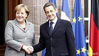 German Chancellor Angela Merkel and French President Nicolas Sarkozy shake hands