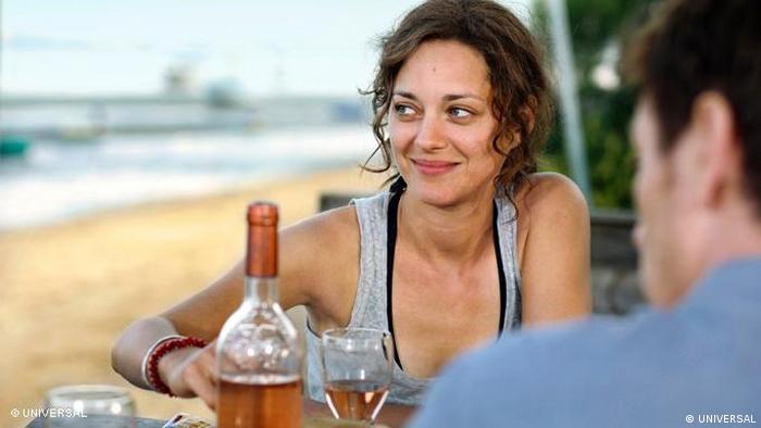 Kleine wahre Lügen - Szene mit Marion Cottilard an sommerlichem Tisch am Strand (Film) (UNIVERSAL)