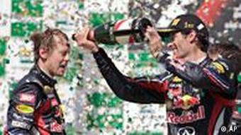 Red Bull driver Mark Webber of Australia pours champagne on teammate Sebastian Vettel, of Germany, during the podium ceremony after a Formula 1 race