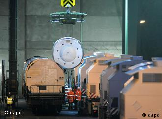 A crane lifts nuclear waste containers onto specially equipped trucks