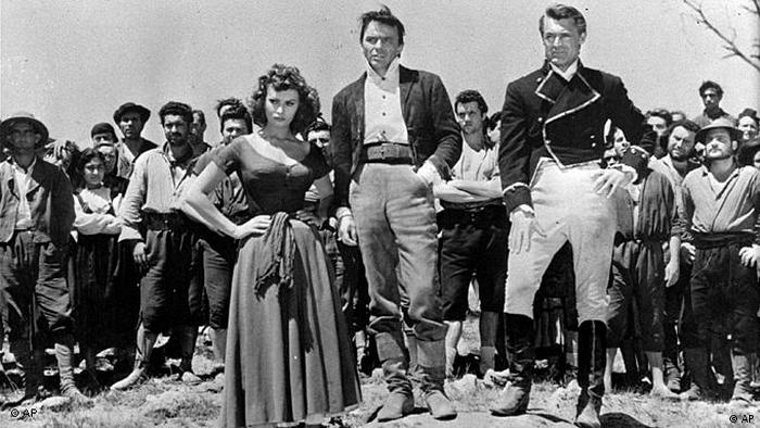 Sophia Loren steht mit zwei uniformierten Männern vor eine Gruppe von Männern.