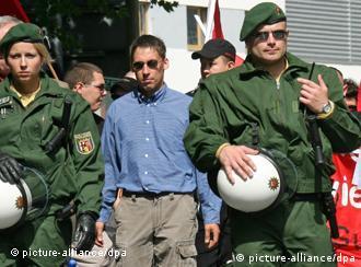 ARCHIV - Der frühere NPD-Funktionär Ralf Wohlleben (M.) flankiert von Polizisten, aufgenommen am 18.08.2007 während einer NPD-Demonstration in Jena. Mit Wohlleben ist am Dienstagmorgen (29.11.2011) ein weiterer mutmaßlicher Neonazi-Terrorist festgenommen worden. Er sei dringend verdächtig, die Gruppe «Nationalsozialistischer Untergrund» (NSU) unterstützt zu haben, teilte die Bundesanwaltschaft in Karlsruhe mit. Ihm wird Beihilfe zu sechs Morden und einem versuchten Mord vorgeworfen. Der 36 Jahre alte Deutsche soll seit 1995 in rechtsextremistischen Kreisen in Thüringen aktiv gewesen sein; seit den 90er Jahren soll er in engem Kontakt mit den drei NSU-Mitgliedern gestanden haben. Foto: Martin Schutt dpa/lth (zu dpa 0250 am 29.11.2011) +++(c) dpa - Bildfunk+++