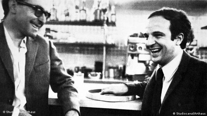 Jean-Luc Godard and Francois Truffaut at a counter, laughing