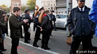 A protester in cuffs is led to a paddy wagon