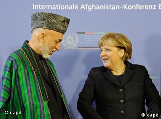 President Hamid Karzai of Afghanistan and German chancellor Angela Merkel, right, meet at the international Afghanistan conference in Bonn, Germany, Monday, Dec. 5, 2011. A decade after the first Afghanistan conference the international community discusses the future of its engagement in Afghanistan. (Foto:Martin Meissner/AP/dapd)
