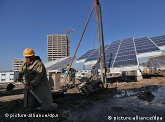 epa03019484 Chinese workers laboring at a construction site where large solar panels are installed in the Sino-Singapore Tianjin Eco-city in Tianjin Binhai New Area, China, 30 November 2011. A joint project by the Singapore and Chinese government, the Sino-Singapore Tianjin Eco-city is a 30 square kilometer development built with the latest green technologies and to serve as a model for future eco-cities in developing countries. With the capacity to accommodate 350,000 people, the eco-city features energy efficient buildings and use of renewable energy power sources such as solar, wind and geothermal energy. Countries are engaged in climate change talks in Durban aimed at cutting global carbon emissions of which China's position is key as the world's largest emitter of greenhouse gases. EPA/HOW HWEE YOUNG