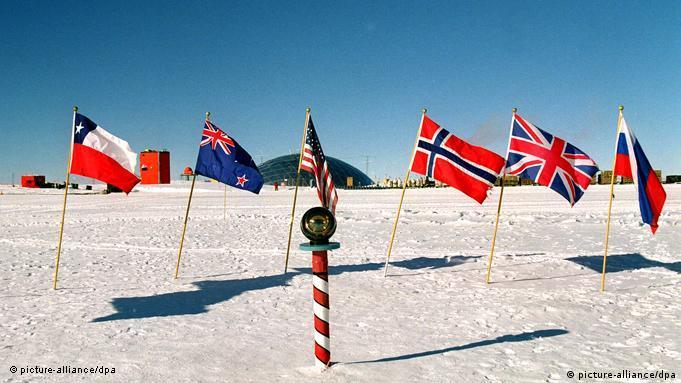 Столб, отмечающий Южный полюс. Флаги стран-покорителей