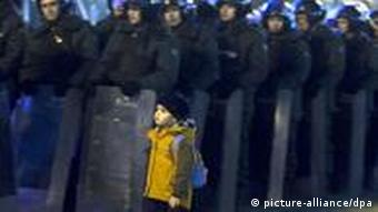 A small boy walking past a row of riot police