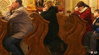 Worshippers pray in church pews