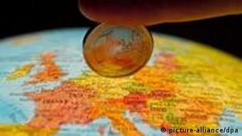 A euro coin held over a globe showing Europe