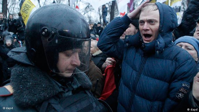Polizist mit schwarzem Helm steht Demonstrant gegenüber (Foto: AP/dapd)