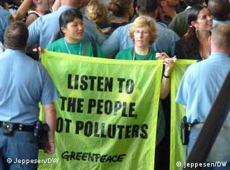 Greenpeace protesters hold sign reading listen to the people not pollutors