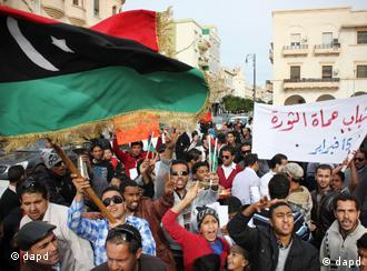 Men chant slogans during a protest in Benghazi, Libya, Monday, Dec. 12, 2011. Arabic writing on the banner, right, reads Libyan youth will protect the revolution, Feb. 15 (Foto: Ibrahim Alaguri/AP/dapd)