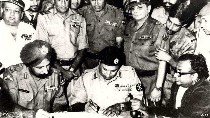 Lt. Gen. Jagjit Singh Aurora, seated left, looks on as Lt. Gen A.A.K Niazi of Pakistani army signs the surrender document, at Dhaka, Dec. 16, 1971 (Photo: AP Photo/Indian Defense Ministry/HO)
