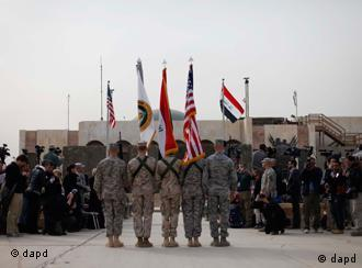The US flag, Iraq flag, and the US Forces Iraq colors are seen before they are carried in during ceremonies marking the end of the US military mission