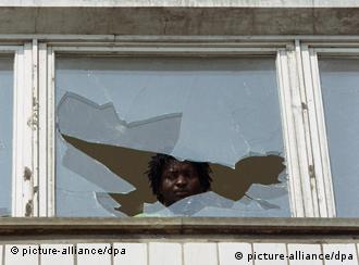 ARCHIV - Ein Asylbewerber schaut am 23. September 1991 aus einem eingeschlagenen Fenster des Asylbewerberheims im sächsischen Hoyerswerda. Als 1991 in Hoyerswerda Molotow-Cocktails gegen Asylbewerberheime flogen, begann in Deutschland eine Serie von rassistischen Pogromen. Als Gegenbewegung gründete sich damals das Bündnis der Vernunft, das jetzt 20-jähriges Bestehen feiert. Foto: dpa +++(c) dpa - Bildfunk+++