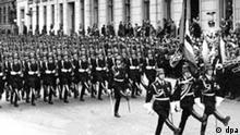 Mitglieder der SS marschieren an Adolf Hitler, der seinen rechten Arm zum Gruß erhoben hat (Bildrand links), vorbei. Aus den umliegenden Fenstern hängen Hakenkreuz-Fahnen. Aufgenommen am 20.4.1939, seinem 50.Geburtstag. Die Schutzstafel, kurz SS genannt, wurde 1925 zum Schutz von Hitler und anderen Funktionären der NSDAP gegründet.