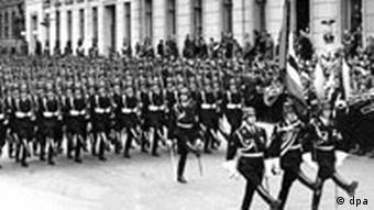 Black and white image of Nazi soldiers marching at a parade for Hitler