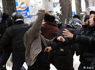 Kazakh riot police officers detain demonstrators during an opposition rally