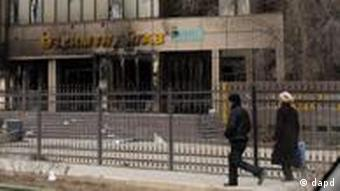 Residents walk past a burnt UzenMunaiGas office in Zhanaozen