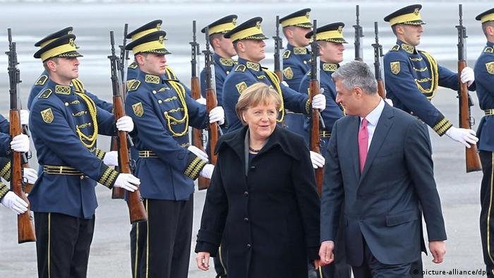epa03038658 German Chancellor Angela Merkel (L) inspects a guard of honor together with Kosovo's Prime Minister Hashim Thaci (R) ahead of their meeting in Pristina, Kosovo, 19 December 2011. EPA/VALDRIN XHEMAJ