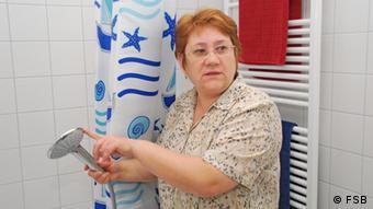 Energiesparberaterin Sofia Prokudina erklärt den wassersparenden Duschkopf Copyright: FSB Datum: 2011 Die FSB stellt die Fotos der Deutschen Welle unbegrenzt zur Verfügung *** eingestellt Dezember 2011